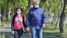мужчина и женщина в масках идут по улице
