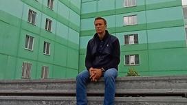 Алексей Навальный сидит на фоне многоэтажки