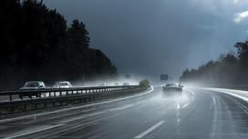 Автомобиль едет по дороге в дождь