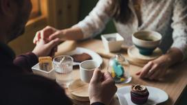 Мужчина и женщина сидят за столиком в кафе