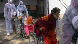 Больные КВИ на колясках с масками на лице и врачи