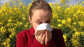 Девушка в красном пальто чихает из-за растения