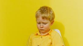 Мальчик в желтом сидит на стуле