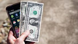 Мужчина сравнивает телефон и деньги