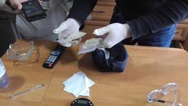 Эксперт держит в руках свертки с наркотическим веществом