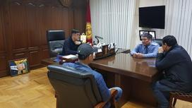 Курсан Асанов и еще несколько мужчин сидят за столом