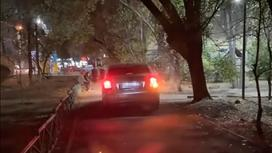 Автомобиль едет по пешеходной дороге в Алматы