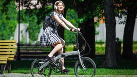 Девушка едет на складывающимся велосипеде