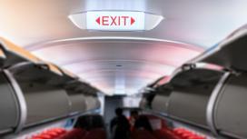 Знак выхода в салоне самолета