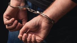 Руки мужчины в наручниках, сведенные за спиной