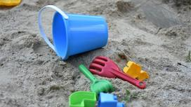 Игрушки лежат в песочнице