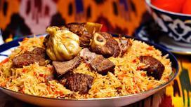 Плов с кусочками мяса и чесноком на тарелке