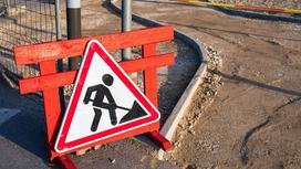 Знак проведения дорожных работ прислонен к красной стойке