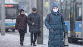 Женщина в синем пуховике идет по улице