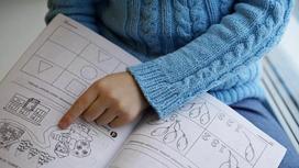 Девочка показывает пальцем в тетрадь