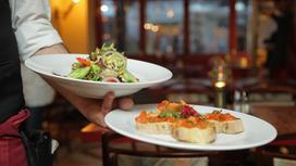 Официант держит в руке две тарелки