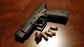 пистолет с патронами лежит на столе