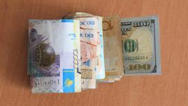 Купюры тенге лежат вместе с долларом на столе
