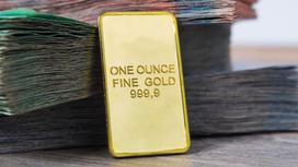 Золотой слиток стоит рядом с пачками тенге