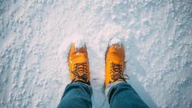 Человек в желтых ботинках стоит на снегу