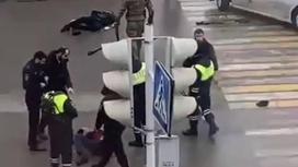 Полицейские стоят рядом с раненным мужчиной