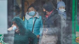 Женщины в масках выходят из автобуса