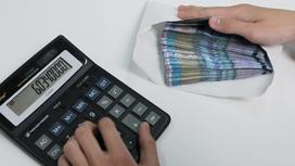 Мужчина открывает рукой конверт с деньгами