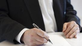 Мужчина в костюме подписывает документ