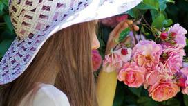 Девушка в шляпе нюхает цветы