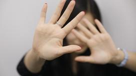 женщина закрывается руками от нападающего