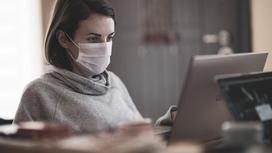 Девушка в маске за компьютером