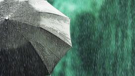 Человек стоит с черным зонтом во время дождя
