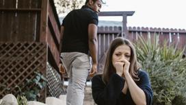 Сидящая с грустным лицом девушка и уходящий от нее мужчина