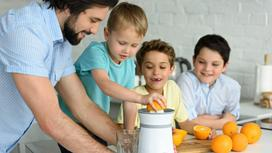 Мужчина и мальчики готовят сок из апельсинов