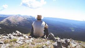 Турист сидит на горе
