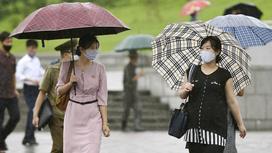 Две женщины идут под зонтами