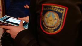 Полицейский держит в руках телефон