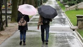 Люди идут под дождем