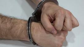 Мужчина в наручниках сидит за столом