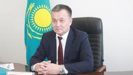Жаксылык Шалабеков сидит за рабочим столом