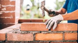Мужчина строит стену из кирпичей