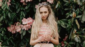 светловолосая девушка на фоне цветов