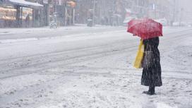 Женщина с красным зонтом стоит на дороге в городе