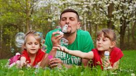 Отец с дочками делают мыльные пузыри