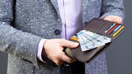 Мужчина держит в руках кошелек с деньгами