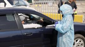 медик в защитном костюме стоит рядом с машиной