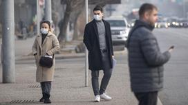 Люди в масках стоят у дороги