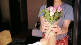 Мужчина дарит женщине букет цветов