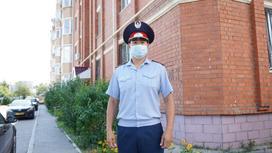 Полицейский в медмаске стоит у дома