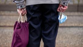 Пожилой мужчина с сумкой в руках стоит на улице